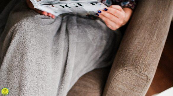Vrouw zittend op de bank met een deken en een tijdschrift