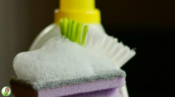 Een stapel paarse schuursponsjes, een afwasborstel en wat sop
