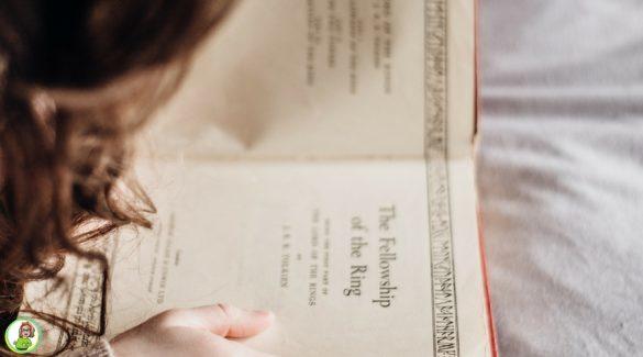 Kind lees een boek in kleermakerszit in bed