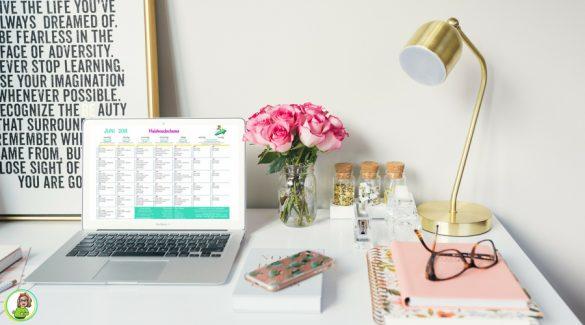 Een bureau met accessoires en een laptop met het huishoudschema juni 2018 van Firma Huishouden
