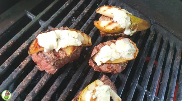Barbecue rooster met daarop vier biefstukken met gegrilde peer en blauwe kaas gesmolten.