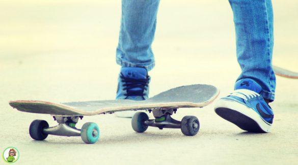 Benen van een tiener in spijkerbroek met gympen en daarvoor een skateboard