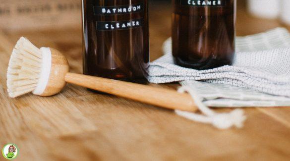 Een houten werkblad met afwasborstel, een vaatdoek en twee spuitflessen homemade schoonmaakmiddel.
