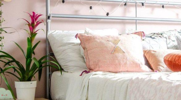 Een bed met kussens en er naast een Bromelia
