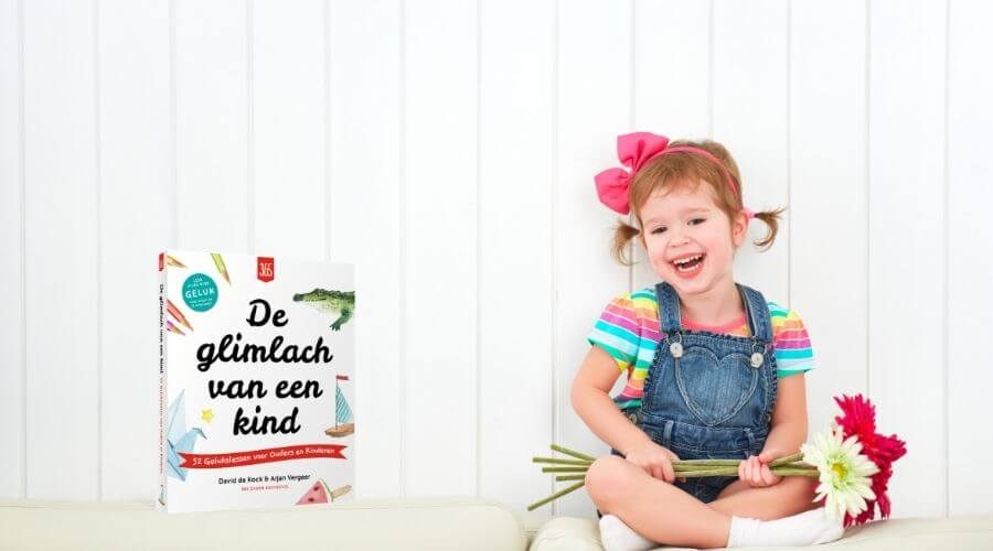 Happy child laughing little girl with a bouquet of gerbera flowers in the empty white wall - Boek over gelukkige kinderen