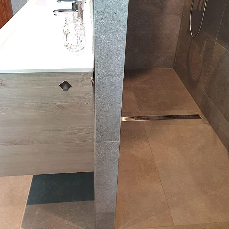 Badkamer met een wand, aan de ene kant een dubbele douche, aan de andere kant badkamermeubelen