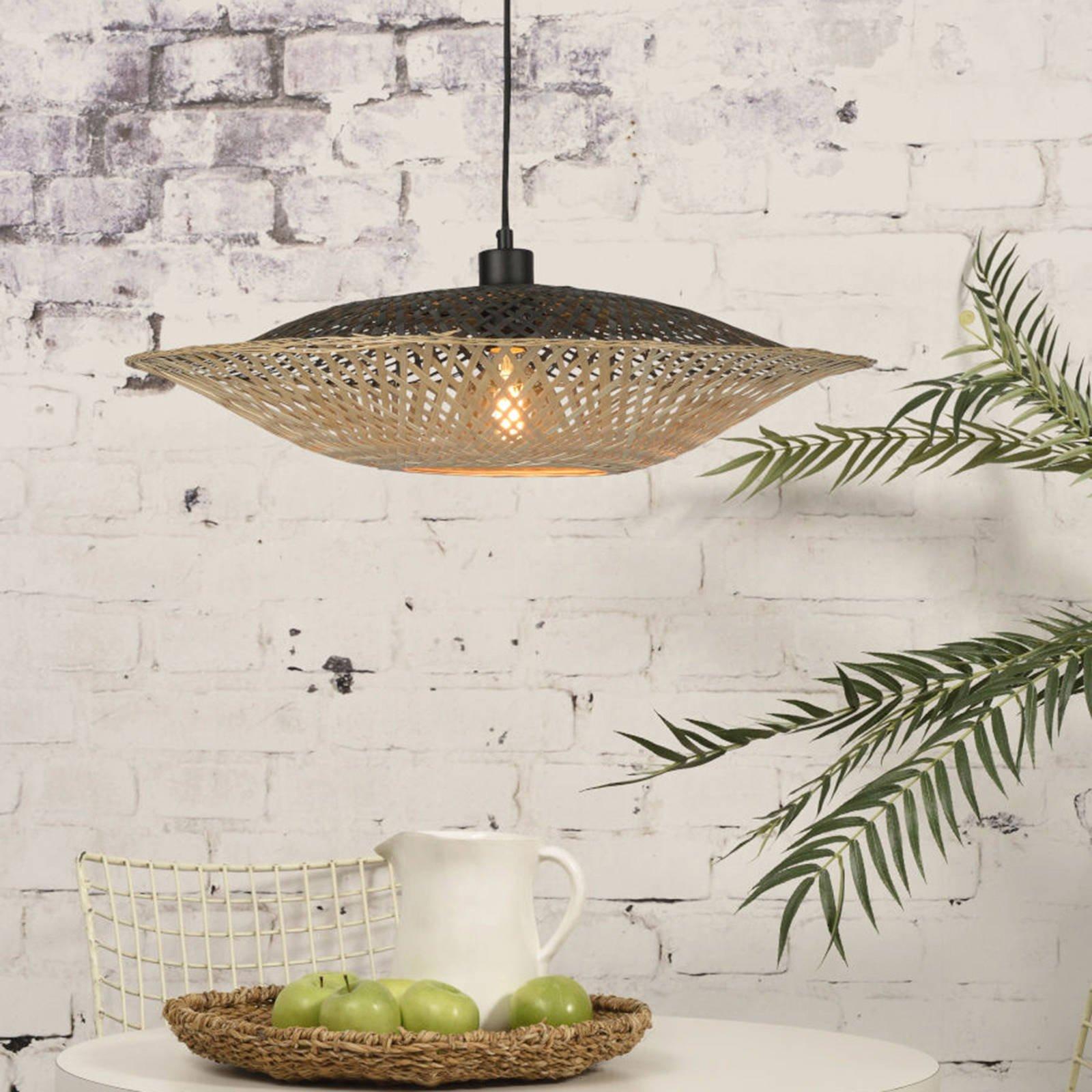 Hanglamp van bamboe, takken van een plant en een fruitschaal op een tafel.
