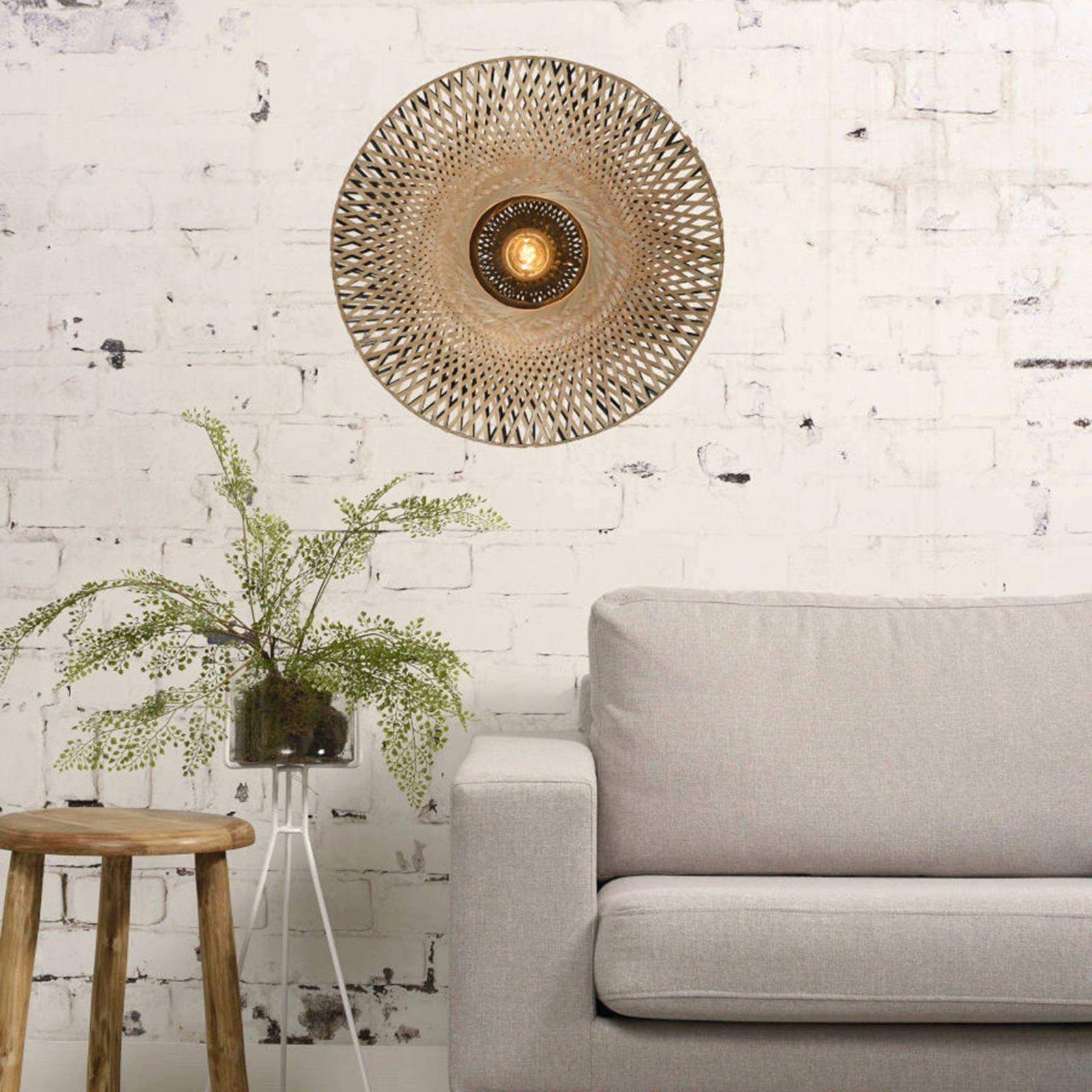 Ronde wandlamp van bamboe, een bank en een plant