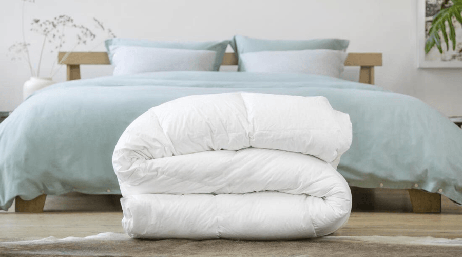 Donzen dekbed opgevouwen op de grond voor een bed