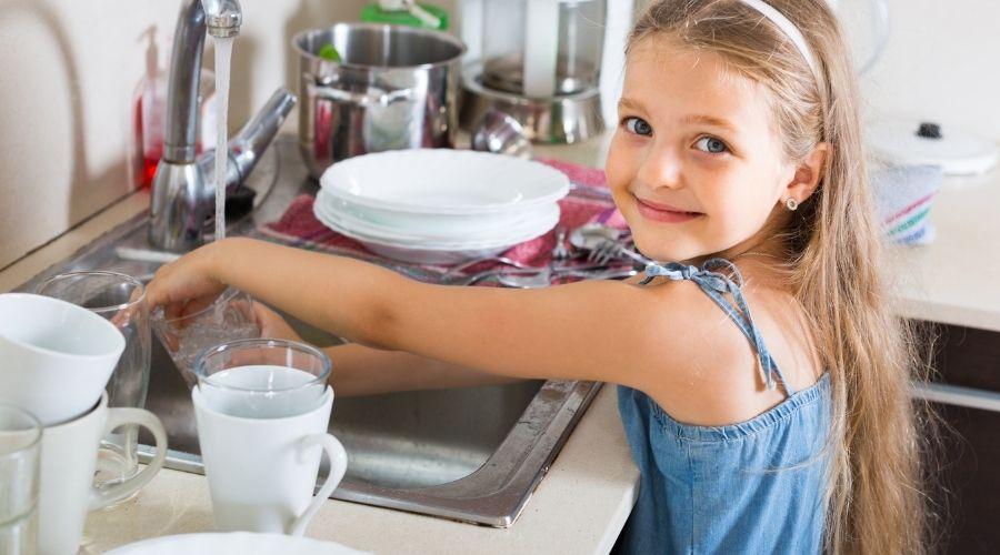 Kind aan de afwas, afbeelding bij artikel: 6 Huishoudelijke basisregels die je kind moet weten